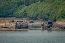 Dilapidated Old Swing Bridge and Fishing Trawler on a River, Britain