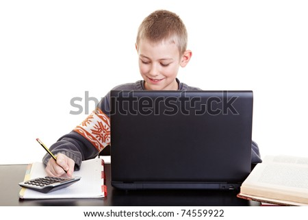 Diligent boy sitting at desk doing his homework and working with laptop