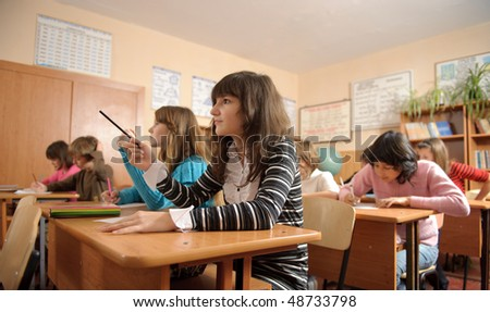 Diligent schoolchildren during lesson. Cute girl on foreground