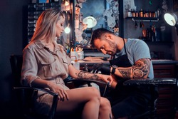 Dilligent focused tattoo artist is creating new tattoo on young woman's hand at tatoo studio.