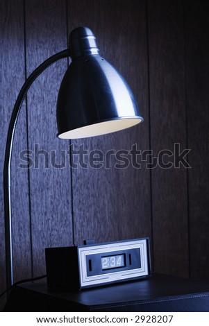 Dim desk lamp and retro clock against wood paneling at night.