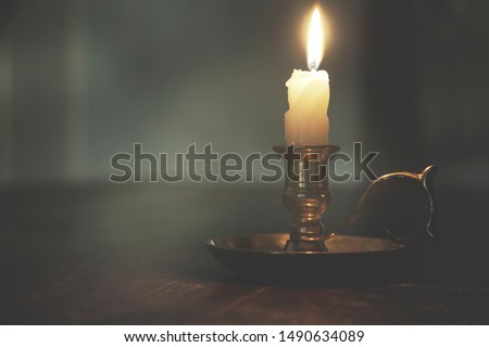 dim light of a candle in a mysterious night, concept of spirituality and hope