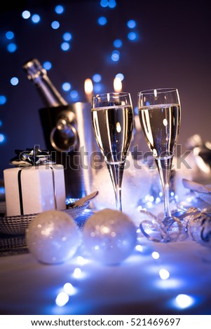 dim light white silver and blue romantic new year eve or christmas table in a luxury restaurant with champagne #521469697
