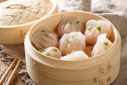 Dim Sum in bamboo steamer, Chinese cuisine. Closeup rustic style. horizontal