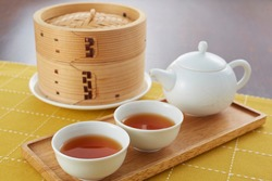 Dim sum set and Chinese tea. it is prepared as small bite-sized portions of food served in small steamer baskets or on a small plate