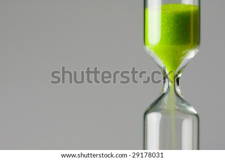 Diminishing green. Ecology / environment concept image. Green sand of hour glass falling down.