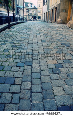 Diminishing view of old european street with cobblestone close-up(Vienna,Austria). Selective focus