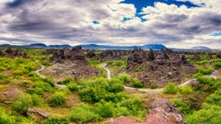 Dimmuborgir lava fields near Myvatn in Iceland. Amazing nature landscape, panoramic view of popular tourist attraction - green valley, rock formations and blue cloudy sky, outdoor travel background