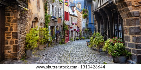 Dinan, traditional colorful houses on a cobbled street in medieval town center, Brittany, France