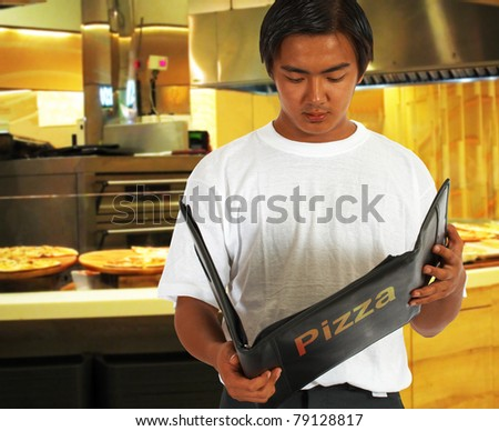 Diner Selecting Food From The Pizza Menu At A Pizzeria
