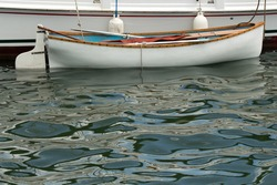 Dinghy of the Wilma Lee on calm blue waters of Silver Lake in Ocracoke Village on the Outer Banks of North Carolina
