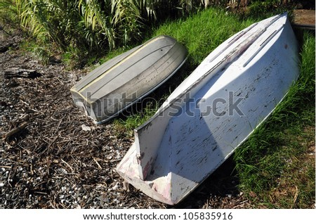 Dingy boats rest on shore of Mangonui Harbor, Northland, New Zealand.