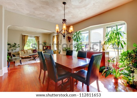 Dining and living room with plants and hardwood floor.