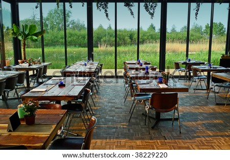 Dining hall with glass walls overlooking a wet garden