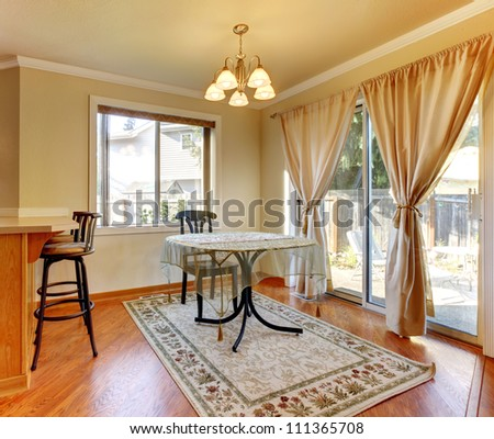 Dining room area with doors and window and simple round table and hardwood floor.