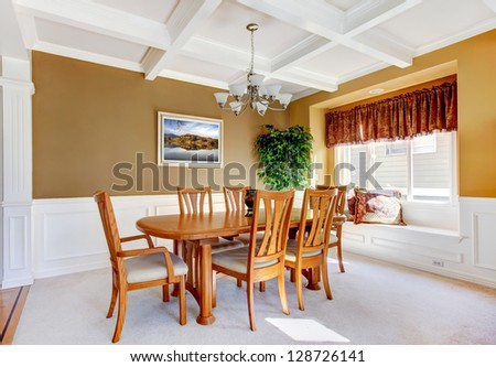 Dining room interior with white bench and wood table.
