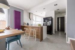 Dining room, kitchen and entrance in contemporary family house with minimalist gray design, colorful accents and wooden furniture