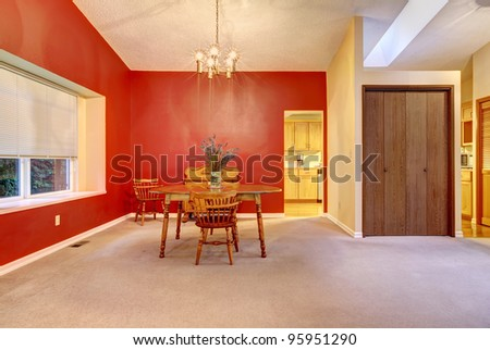 Dining room that is part of the living room with red wall and kitchen view.