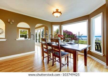 Dining Room With Brown Walls And Wood Table With Water View. Stock ...