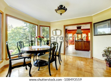 Dining room with large windows and hardwood floor.