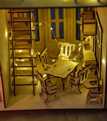Dining room with table, chairs and a kitchen wall in an assembled house made of plywood with yellow lights conveys comfort of the hearth