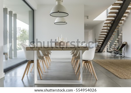 Dining room with window, ceiling lamp and stairs #554954026