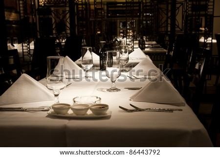 dining setup with wine glasses silver cutlery  and white napkins in a modern restaurant