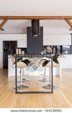 Dining Table And Bar Stools On Wooden Floor In Open Space With Designed Kitchen