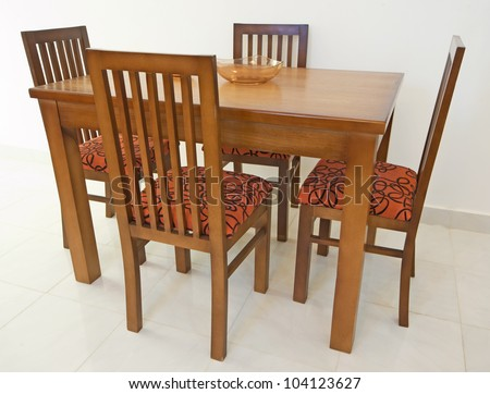Dining table and four chairs in an apartment against white wall
