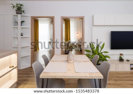 Dining table between kitchen and living room in contemporary apartment #1535483378