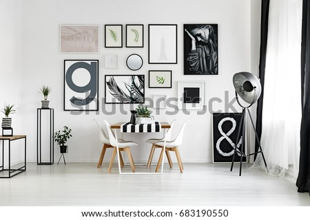Dining table by the white wall with posters in spacious lounge #683190550