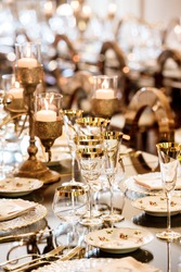 Dining table decorated with bronze candelabra and gilded wine glasses, festive candlelight Christmas feel
