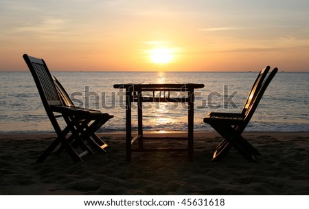 Dining table on a beach close to the ocean