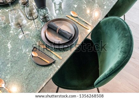 dining table setup with golden cutlery and green suede chair