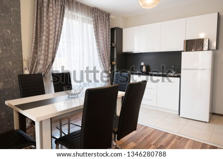 Dining table with set of chairs near the large window in kitchen #1346280788
