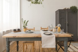 dining wooden table and chairs in modern home with elegant table setting