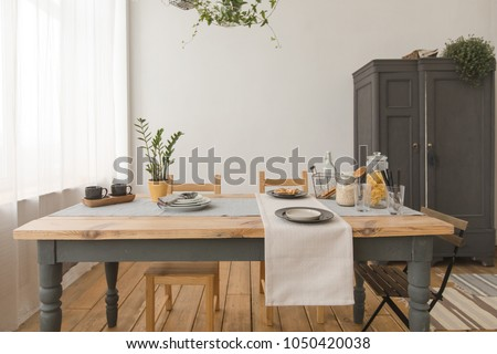 dining wooden table and chairs in modern home with elegant table setting #1050420038