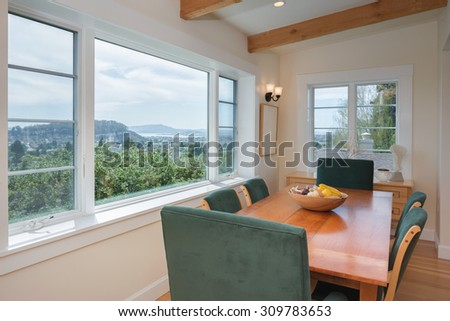 Dining wooden table and chairs with view window. Dining table with chairs, wooden floor, beamed ceiling in luxury home.