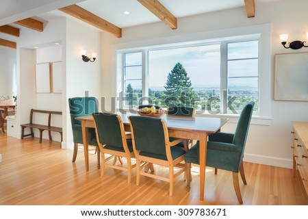 Dining wooden table and chairs with view window. Dining table with chairs, wooden floor, beamed ceiling in luxury home. Spacious dinning room in modern house.