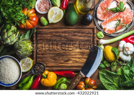 Dinner cooking ingredients. Raw uncooked salmon fish steaks with vegetables, rice, herbs, spices and wine , rustic wooden chopping board in center, top view, copy space