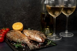 Dinner for two. Grilled dorado fish with spices and a bottle of white wine with glasses on a stone background