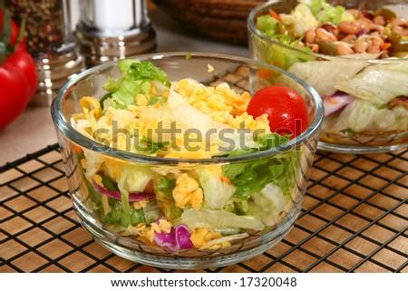 Dinner garden salad in glass bowl in kitchen or restaurant.