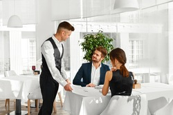 Dinner In Restaurant. Waiter Serving Happy Romantic Young Couple In Love. Cheerful People Making Orders, Celebrating Anniversary Or Valentine's Day. Love, Romance, Relationships Concept.