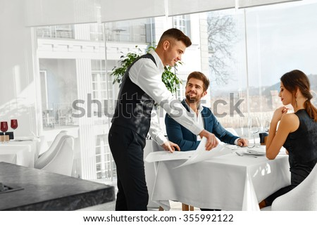 Dinner In Restaurant. Waiter Serving Happy Romantic Young Couple In Love. Cheerful People Making Orders, Celebrating Anniversary Or Valentine's Day. Love, Romance, Relationships Concept.  #355992122