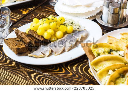 Dinner in russian restaurant - small fried potato dusted with greens and salted herring fish with bread toasted on a white plate on a brown wooden table