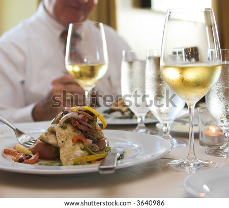 dinner of sauteed flounder and white wine with man eating in background, focus on foreground