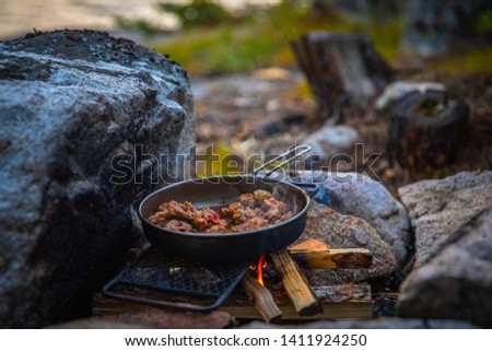 Dinner over the campfire in the wilderness.  Wood fire cooked sausage, Canadian wilderness #1411924250