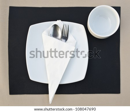 Dinner place setting. A white plate with stainless fork and cup