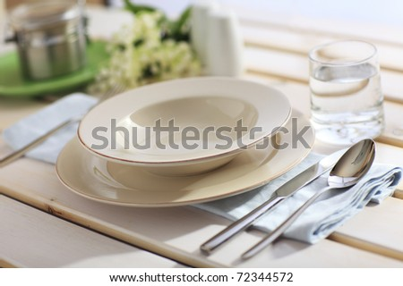 Dinner Place Setting On A Garden Table with Silver Spoon And Knife, Blue Napkin And Plates