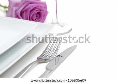 Dinner place setting. white china plates with pink rose and silver knife and fork